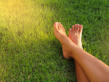 Bare foot lying on green grass. Stock Photo