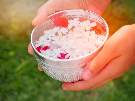 Woman hand holding a silver bowl of jasmine water for Songkran festival in summer season Thailand
