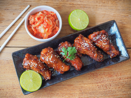 Korean style spicy sauce deep fried chicken wing serve with kimchi