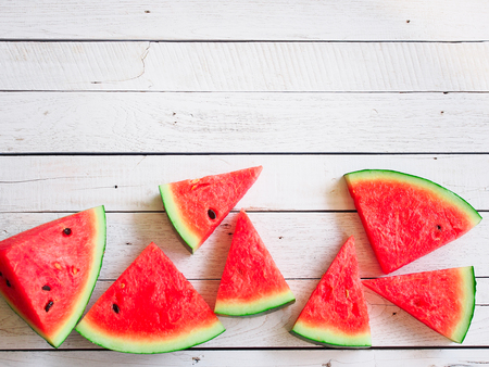 Sliced watermelon flay lay on wooden white in summer beach concept with copy space