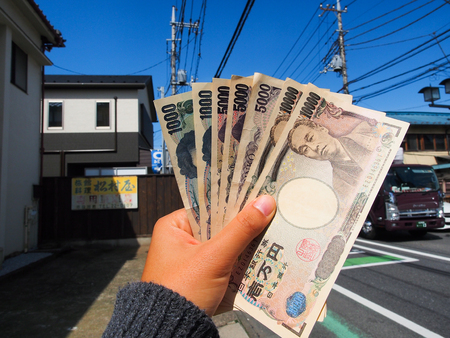 Woman hand holding  japan yen banknote ready to spend money for travel trip Stock Photo