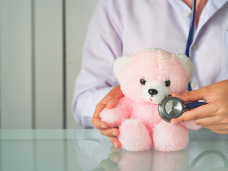 Doctor use stethoscope checking heart on pink bear for healthcare concept with copy space.