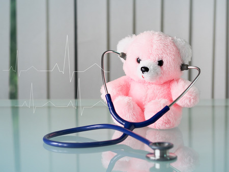 Pink bear with stethoscope and  electrocardiogram graphic for healthcare concept.