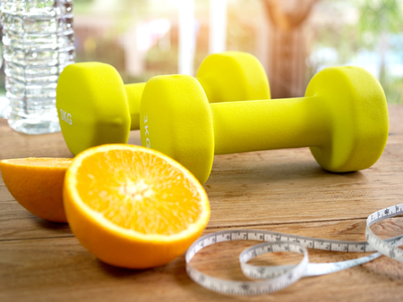 Dumbbells,orange,bottle of water and measuring tape for fitness and healthy lifestyle concept.