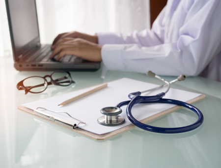 Stethoscope,clipboard and doctor working on laptop in hospital for health care concept.