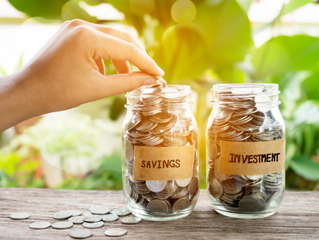 Woman hand putting  coin into glass jar for savings money concept.