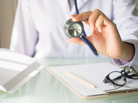 Doctor holding stethoscope in hand for health care concept.