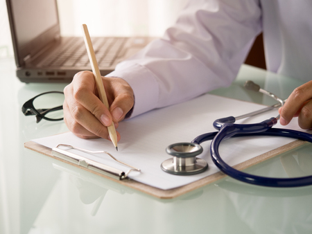 Doctor write something on paper,working in hospital for health care concept.