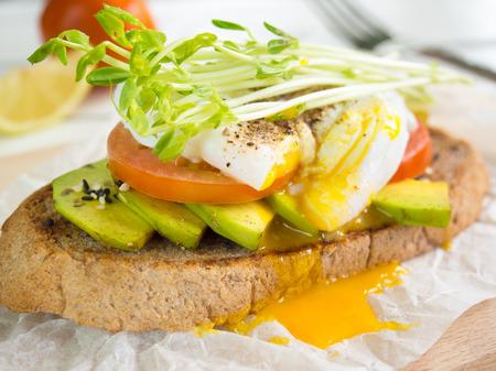 半熟卵、トマトとアボカド、健康的な朝食のもやしトッピング全粒小麦のトースト。