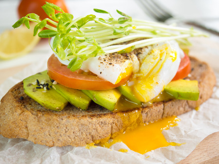 bean sprouts: poached egg,tomato and avocado on whole wheat toast topping with bean sprouts for healthy breakfast.