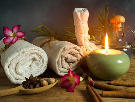 Spa-massageartikelen, aroma-olie, kruiden-comprimeerkogel en handdoek bij kaarslicht. Stockfoto