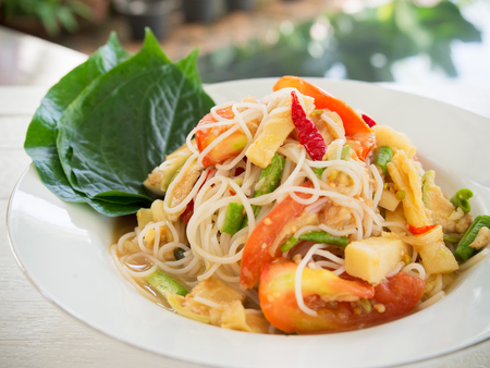 Spicy papaya salad with rice noodle or somtum famous  traditional Thai food.