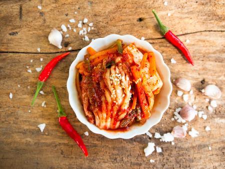 Kimchi, gefermenteerde kool traditionele Koreaanse gerechten in bovenaanzicht op houten tafel.
