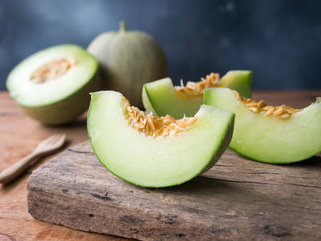 Fresh japanese green melon fruit sliced on wooden cutting board.