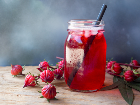 Iced roselle tea glass  with fresh roselle fruit  on wooden table  for healthy herbal drink concept.