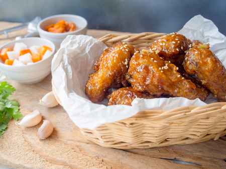 Deep fried chicken wing with garlic sauce in Korean style serve with kimchi and pickled radish. Reklamní fotografie