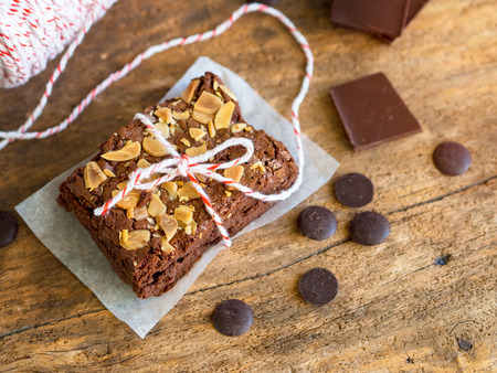 Fudge brownies chocolate cake topping with almond sliced on wooden table for winter bakery concept. Reklamní fotografie