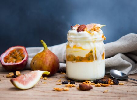 Granola yogurt with passionfruit and fig in jar for healthy breakfast or clean food concept. Reklamní fotografie