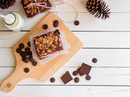 Fudge brownies chocolate cake topping with almond slice on wooden chopping board for winter bakery concept in top view with copy space.