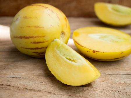 Fresh pepino melon fruit on wooden table.