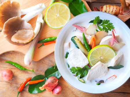 Thai galangal chicken soup in creamy  coconut milk or Tom Kha Gai, famous traditional Thai food  in top view on wooden table background with ingredients.