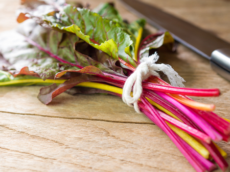 Fresh rainbow swiss chard vegetable on wooden board preparing for cooking.