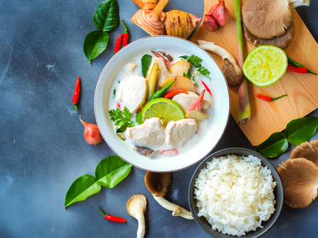 Thai galangal chicken soup in coconut milk or Tom Kha Gai, famous traditional Thai food serve with jasmine steam rice in top view on gray background with ingredients.