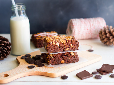 Fudge brownies chocolate cake topping with almond slice on wooden chopping board for winter bakery concept . Stock Photo