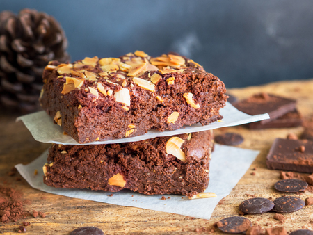 Fudge brownies dark chocolate cake topping with almond slice on wooden table for winter bakery concept.