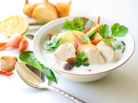 Thai galangal chicken soup in creamy  coconut milk or Tom Kha Gai,famous traditional Thai food on white background  with ingredients.
