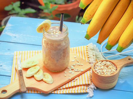 Banana and oats smoothies in glass with fresh banana sliced on blue wooden table  for diet food or healthy drinks concept. Reklamní fotografie