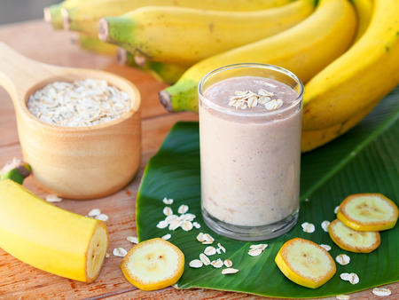 Banana and oats smoothies in glass with fresh banana sliced on wooden table for diet food or healthy drinks concept.