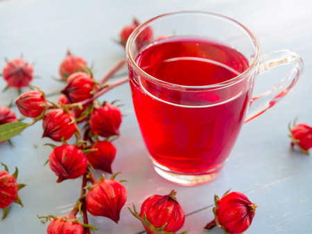Cup of hot  roselle tea with fresh roselle fruit  on wooden table  for healthy herbal drink concept.