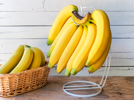 Yellow ripe banana  hanging on hanger with white wooden background.