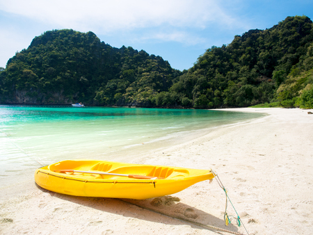 Yellow kayak boat on white sand beach at the sea with mountains view background for summer holiday concept. Stock Photo