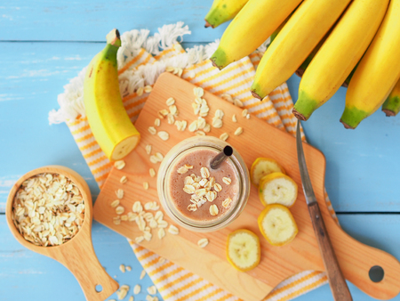 Banana and oats smoothies in glass with fresh banana sliced on blue wooden table in top view for diet food or healthy drinks concept. Reklamní fotografie