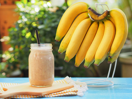 Banana smoothies in glass with fresh bananas hanging on hanger for diet food or healthy drinks concept. Stock Photo