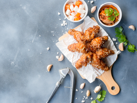 Deep fried chicken wing with garlic sauce in Korean style serve with kimchi and pickled radish on grey background in top view with copy space  for asian food concept. Stockfoto