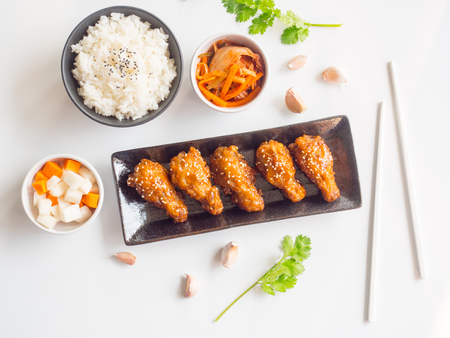 Deep fried chicken wing plate with garlic sauce in Korean style serve with rice, kimchi and pickled radish on white background in top view for asian food concept. Reklamní fotografie - 96710710