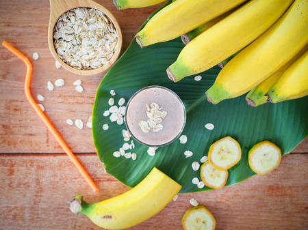 Banana and oats smoothies in glass with fresh banana sliced on wooden table in top view for diet food or healthy drinks concept.