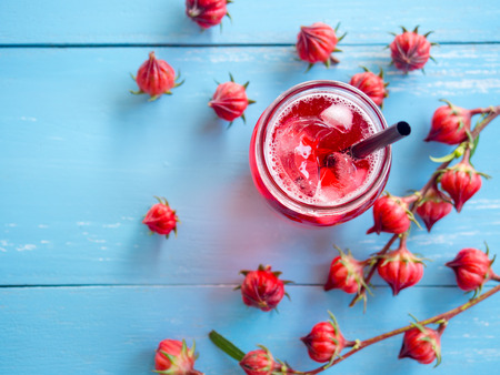 Iced roselle tea glass  with fresh roselle fruit  on blue wooden table  for healthy herbal drink concept. Stock Photo