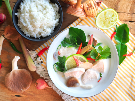 Thai galangal chicken soup in creamy  coconut milk or Tom Kha Gai,famous traditional Thai food serve with jasmine steam rice in top view on wooden table background.