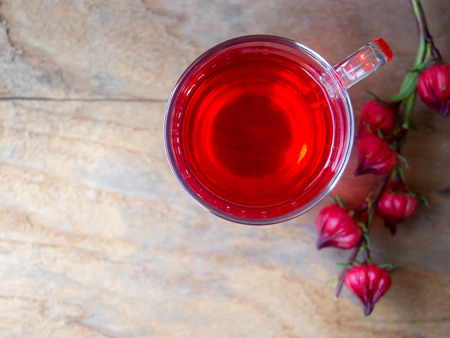 Cup of hot  roselle tea with fresh roselle fruit in top view on wooden table with copy space for healthy herbal drink concept. 스톡 콘텐츠