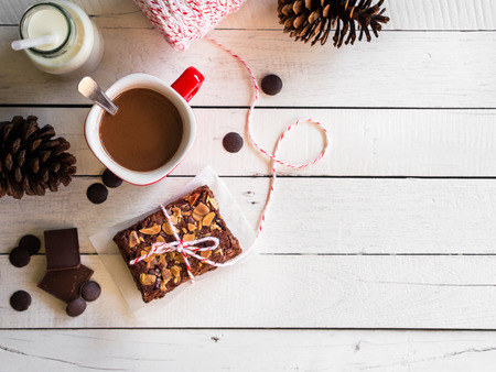 Fudge brownies chocolate cake with coffee cup and bottle of milk on white wooden table in top view with copy space for winter breakfast concept. Reklamní fotografie