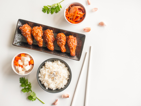 Deep fried chicken wing plate with garlic sauce in Korean style serve with rice, kimchi and pickled radish on white background in top view with copy space  for asian food concept. Stock Photo - 97294513