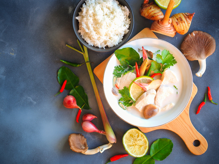 Thai galangal chicken soup in coconut milk or Tom Kha Gai,famous traditional Thai food serve with jasmine steam rice in top view on gray background.