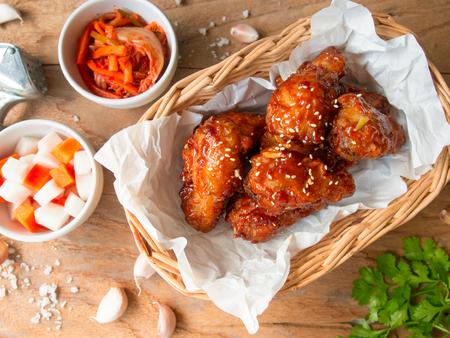 Frittierter Hühnerflügel mit Knoblauchsoße im koreanischen Artaufschlag mit Kimchi und in Essig eingelegtem Rettich in der Draufsicht über Holztisch für asiatisches Lebensmittelkonzept.
