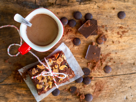 Hot chocolate cup with fudge brownies cake on wooden table in top view with copy space for winter breakfast concept.