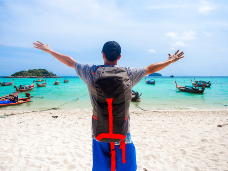asian man backpacker relaxing on the beach and enjoy view of blue sea in sunny summer day for holiday or vacation concept,Koh Lipe island in Thailand. Stock Photo