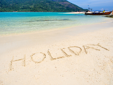 Holiday text on white sand beach with blue sea and mountain background in sunny summer day,Koh Lipe Thailand.